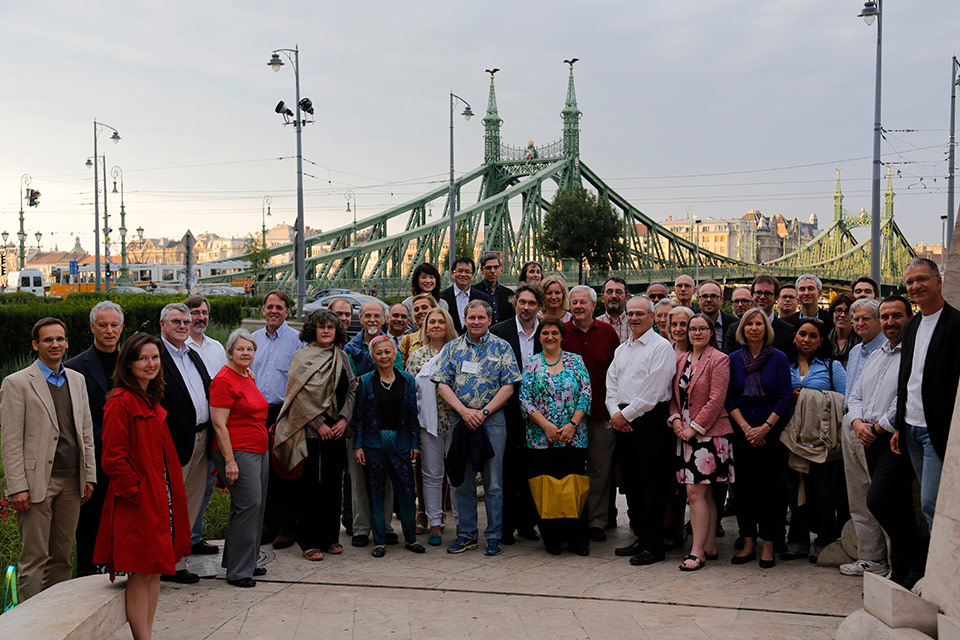 Some 40 people stand up to a photography with a beautiful bridge in the background
