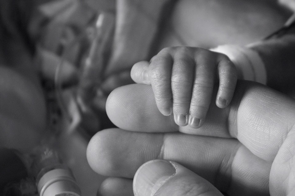 A prematurely born little baby holds his little hand around one of dad's fingers.
