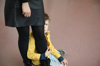 Boy sitting on the floor looking up behind an adult